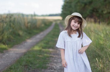 Happy little girl on the road. Cute girl in a white dress stands near field