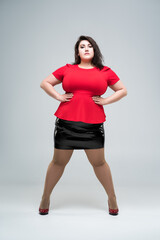 Plus size fashion model in red blouse and black skirt, fat woman on gray background, body positive concept