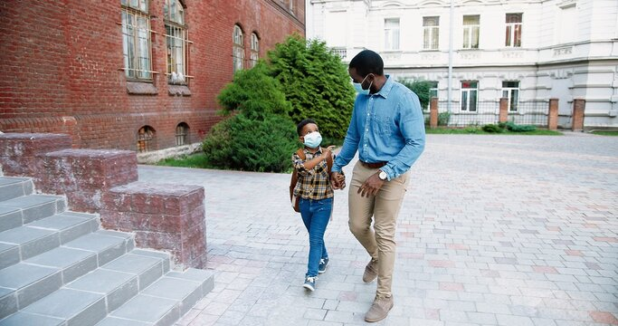African American handsome father in mask brings his son to school after quarantine. Little cute male junior student with backpack running to classes to study. Back to school. Knowledge concept