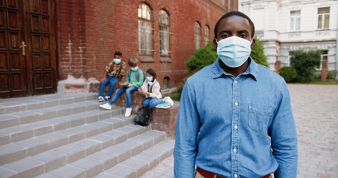 Portrait of African American handsome male teacher in mask looking at camera in front of school. Man standing outdoor at schoolyard. Mixed-races junior students on background. Pandemic concept