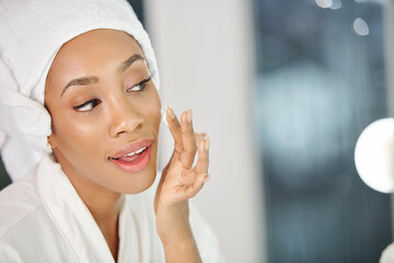 Pretty young Black woman applying moisturizing face lotion after taking shower in the morning