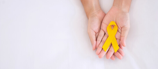Suicide prevention and Childhood Cancer Awareness, Yellow Ribbon for supporting people living and illness. children Healthcare and World cancer day concept