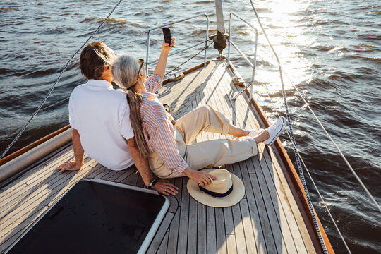 Two senior people sitting together on a yacht bow and taking selfie. Mature couple taking photographs on mobile phone during a boat trip.