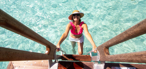 Smiling woman climbs a ladder out of clear turquoise water on the tropical island Bora Bora in French Polynesia