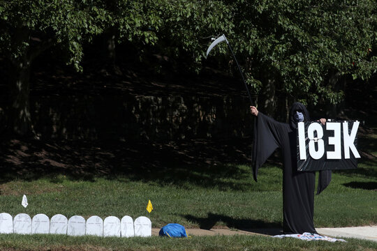 Protester in Grim Reaper costume holds up sign with 183K to represent number of COVID-19 victims in Sterling, Virginia