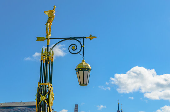Antique lantern with gilt on a pole on the street.