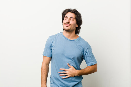 Young handsome man against a white background touches tummy, smiles gently, eating and satisfaction concept.