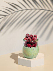 Green matcha overnight oats dressed frozen raspberries. Glass jar with breakfast oats on hexagon pedestal in fashion trendy style with tropical leaf shadow. Modern still life with copy space Vertical