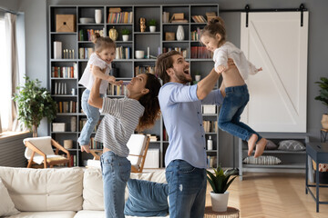 Happy young energetic couple lifting little laughing kids in air, playing together in modern living...