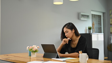 A young woman is using a computer tablet while sitting at a wooden table.