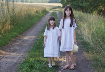 Two happy little girl on the road. Cute smiling girls in a white dresses stand near field