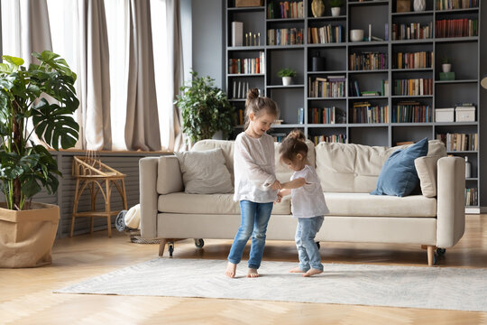 Full length loving small girl holding hands of small toddler sister, dancing barefoot together in floor carpet in living room. Happy two little cute children involved in energetic activity indoors.