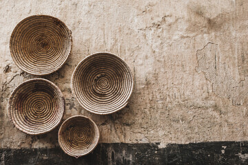 Handmade wicker round baskets hanging on textured wall in Marrakech medina souk. Traditional...