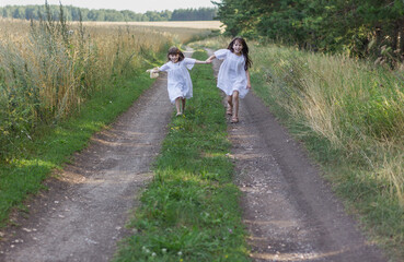 Two cute little girls run on the road. Happy summer time.