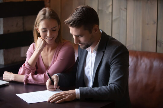Happy young couple making investment deal, smiling wife looking at husband signing contract at meeting, family satisfied customers purchasing new house, first apartment, taking loan or mortgage
