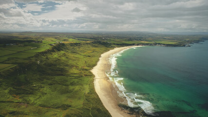 White Beach sand coast aerial zooming, Antrim County, Nortern Ireland. Epic landscape of greenness cliff shore of Atlantic ocean bay. Calm water at dusk cloudy day.