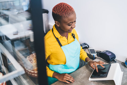 Female worker of pastry shop working with tablet at counter