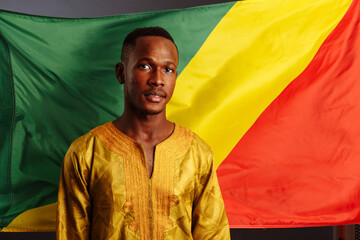 Young man in gold national clothes looking into the camera and posing with Congo Flag isolated in gray Background.