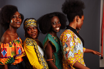 Four young beautiful African fashion models have fun and laughing in traditional dress. Women from the Congo Republic, Ivory Coast, and Zimbabwe