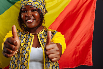 African woman in national clothes posing and dancing with Thumbs up against flag of Congo Republic