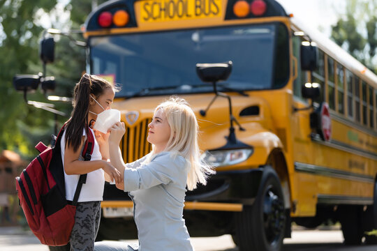 Caucasian woman puts a protective mask on her daughter outdoors. Caring mother helps to wear a mask schoolgirl near the school bus. Quarantine during coronavirus.
