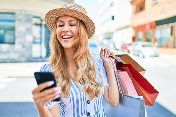 Young beautiful shopper woman smiling happy going to the shops sales holding shopping bags...