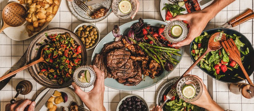 Summer barbeque party. Flat-lay of table with grilled meat, vegetables, salad, roasted potato and peoples hands with glasses of lemon water over white tablecloth, top view, wide composition
