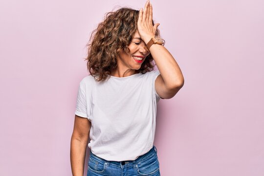 Middle age beautiful woman wearing casual t-shirt standing over isolated pink background surprised with hand on head for mistake, remember error. Forgot, bad memory concept.