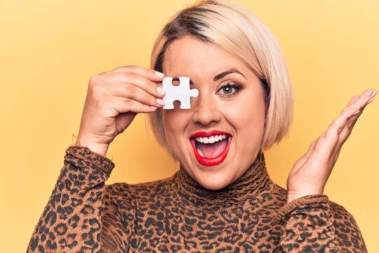 Young beautiful blonde plus size woman holding one piece of puzzle over eye celebrating achievement with happy smile and winner expression with raised hand