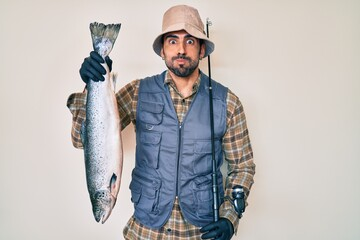 Handsome hispanic man with beard holding fishing rod and raw salmon puffing cheeks with funny face....