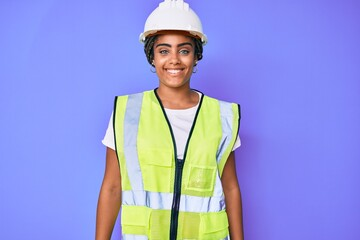 Young african american woman with braids wearing safety helmet and reflective jacket looking positive and happy standing and smiling with a confident smile showing teeth