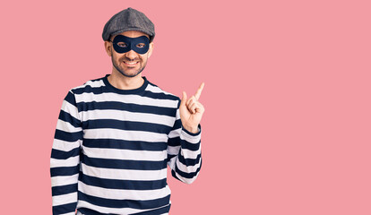 Young handsome man wearing burglar mask with a big smile on face, pointing with hand finger to the side looking at the camera. Papier Peint