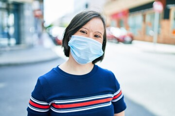 Beautiful brunette woman with down syndrome at the town on a sunny day wearing safety medical mask for coronavirus
