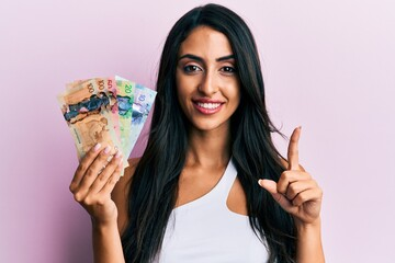 Beautiful hispanic woman holding canadian dollars smiling with an idea or question pointing finger with happy face, number one