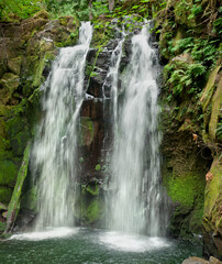 Cascading waterfall with mossy rocks in closeup vertical panoramic view