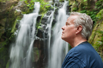 Senior man in nature viewing waterfall landscape