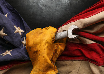 Photo sur Plexiglas Pain Worn work glove holding wrench tool and gripping old worn US American flag. Made in USA, American workforce, blue collar worker, or Labor Day concept.