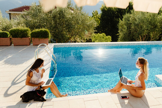 girls using laptop and work remotely on social distance during quarantine. Two women freelancers using devices and work online wearing protective face masks on self isolation at home near pool