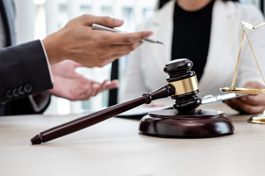 A male lawyer or a judge counseling clients about judicial justice and prosecution with scales, judges gavel, legal documents legal services concept