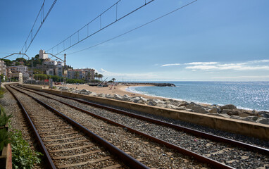 Rail way through a beach to a town with the coast next to it