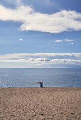 person in the distance sitting alone on the shore of the beach with no one else around