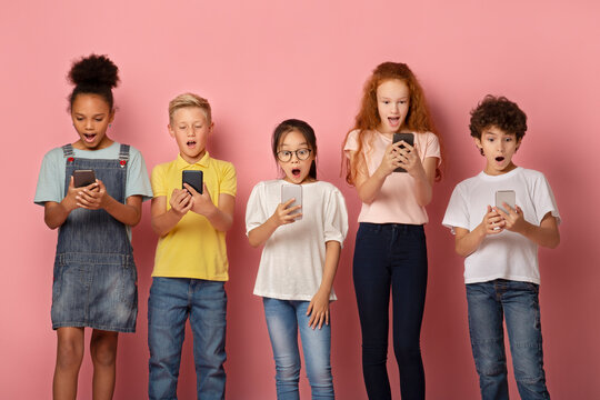 Shocked schoolkids looking into their mobile phones on pink background