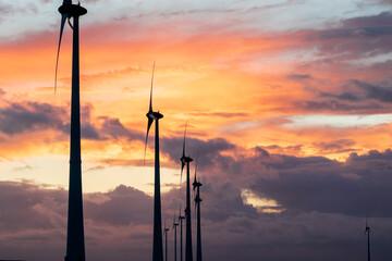 dramatic purple sunset and wind turbines