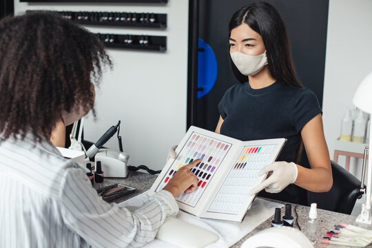 Asian girl in protective mask looks at african american client, chooses color in nail studio interior