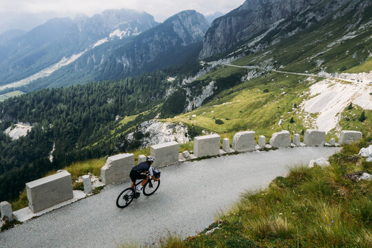 Professional road cyclist on training trip in alps. Amazing epic landscape of mountain road and cyclist on travel tour bike descends steep hill. Inspiring photo of cycling sport