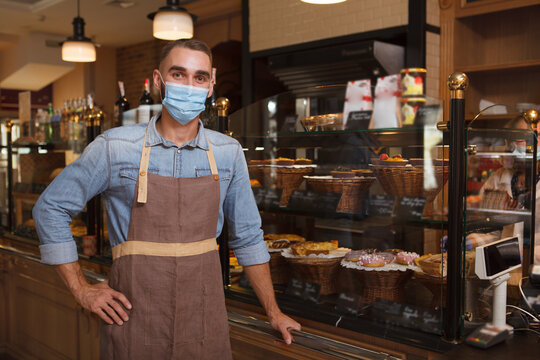 Male baker wearing medical face mask working at his bakery store during coronavirus quarantine