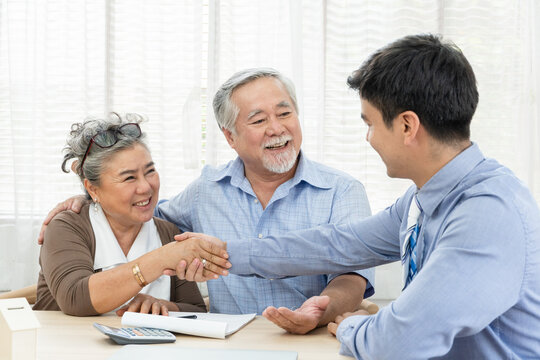 Happy smiling Asian old couple making purchase and mature woman handshake with real estate agent, Sales man closing deal from business agreement contract, concept for retirement or lifestyle insurance