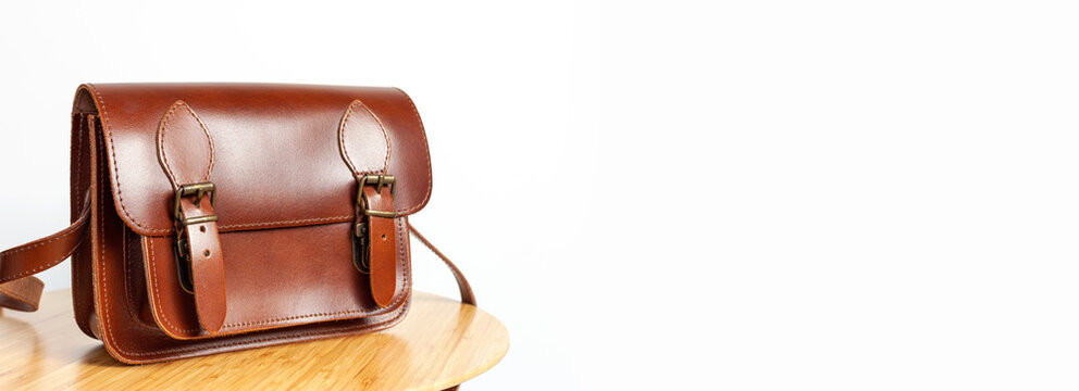 Fashionable brown women's bag made of genuine leather on wooden table against white wall with place for text. Fashion concept. Details of leather bag belt metal buckle clasp. Stylish female accessory