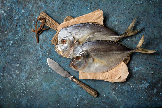 Two whole salty vomer fish on wooden board with vintage knife