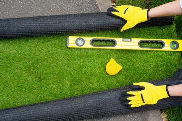 Artificial grass roll and tools in female hands. View above.